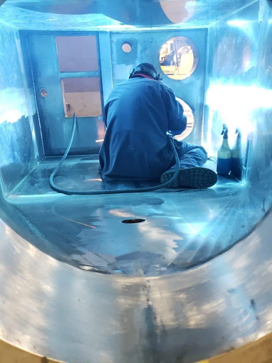 Metal fabricator welding inside an oversized project